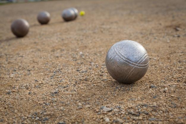 백그라운드에서 다른 금속 공을 모래 피치에 페탕 크 공