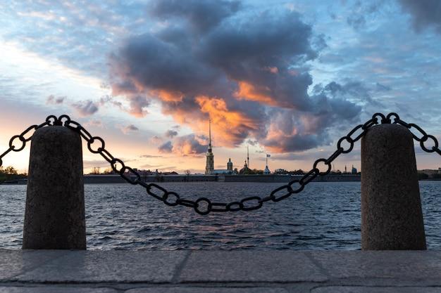 Петропавловская крепость и река нева во время драматического заката в санкт-петербурге. вид с дворцовой набережной /