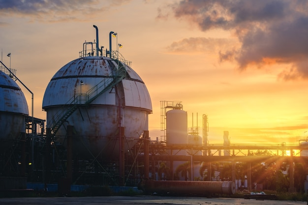 Petrochemical industrial plant on sunset sky background, gas storage chemical industry