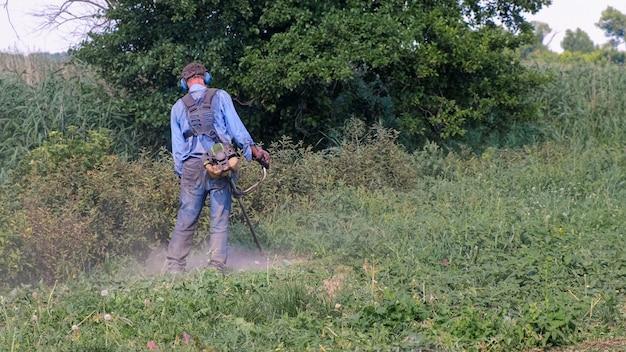 ガソリンブラシカッター。オーバーオール、保護メガネ、防音ヘッドホン、作業用手袋を着用した男性が、ガスカッターで草を刈り取ります。