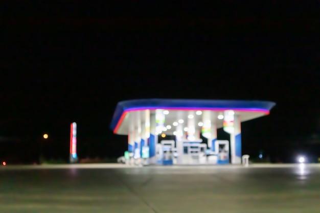 ボケ味でぼやけた夜間のガソリンスタンド