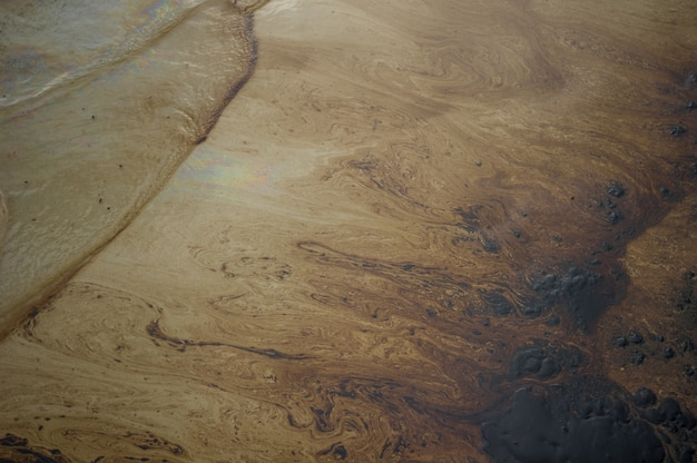 Petroleum spill mixed with other chemical substances on sea and sand surface.