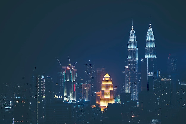 Башни-близнецы петронас (с любовью известные как klcc) и окружающие здания во время заката, видимые со skybar