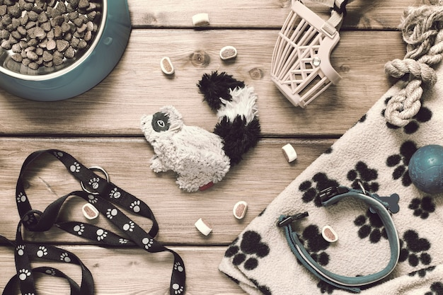 Pets accessories - collar, leash, muzzle, food bowl, toys, mat on a wooden background in vintage style. flat lay