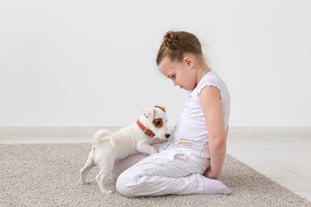 Концепция домашних животных и животных - ребенок девочка играет со щенком джек рассел терьер