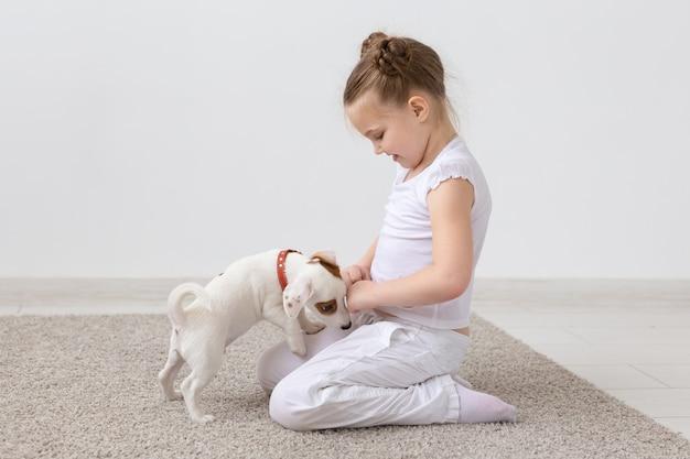 Концепция домашних животных и животных - ребенок девочка играет с щенком джек рассел терьер