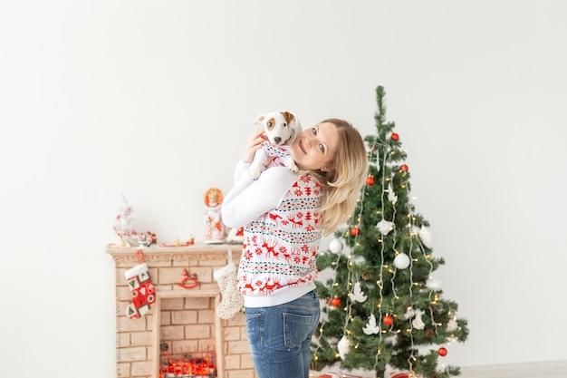 ペットと動物のコンセプト-面白い子犬ジャックラッセルテリアを持つきれいな女性