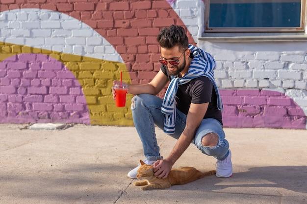 Концепция домашних животных и животных - красивый молодой человек играет с милой рыжей кошкой на открытом воздухе.