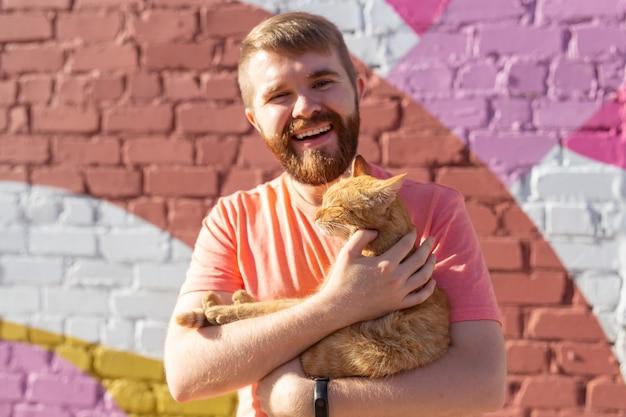 애완 동물 및 동물 개념-야외에서 귀여운 빨간 고양이와 잘 생긴 젊은 남자