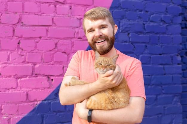 애완 동물과 동물 개념 - 야외에서 귀여운 빨간 고양이와 함께 잘생긴 젊은 남자.