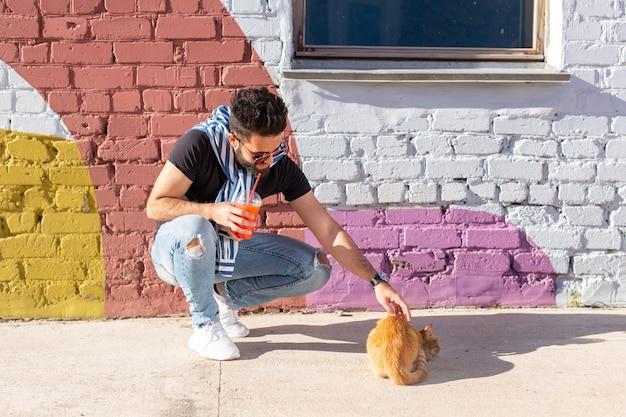 Домашние животные и концепция дружбы - красивый мужчина играет с милой рыжей кошкой на открытом воздухе.
