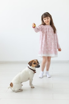 Pets, children and family concept - little girl and her puppy jack russell at studio