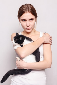 Pets, comfort, rest and people concept - beautiful smiling woman with a kitten in her arms, studio picture, close-up