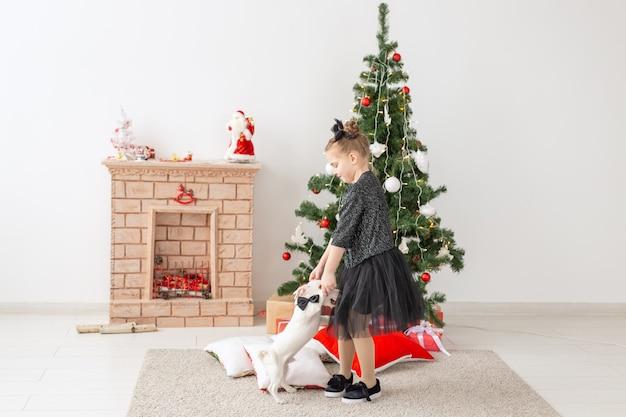 ペット、休日、クリスマスのコンセプト-クリスマスツリーの近くで子犬ジャックラッセルテリアと遊ぶ子供の女の子。