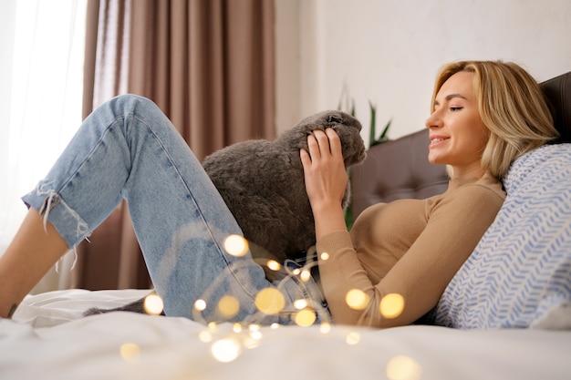 ペット、朝、快適さ、休息と人々の概念-自宅のベッドで猫と幸せな若い女性