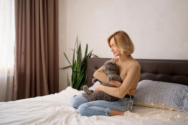 애완 동물, 아침, 편안함, 휴식과 사람들 개념-집에서 침대에서 고양이와 함께 행복 한 젊은 여자