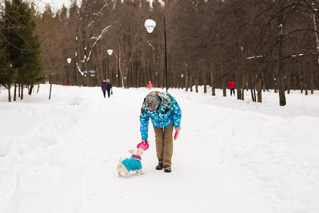ペットの飼い主と冬のコンセプト-雪の中でジャックラッセルテリア犬と遊ぶ中年女性