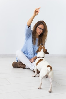 ペットの飼い主のコンセプト-彼女のお気に入りのペットと遊ぶ青いセーターの魅力的な陽気な女性