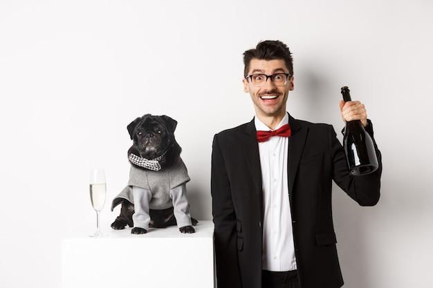 ペット、冬休み、年末年始のコンセプト。クリスマスパーティーを祝って、シャンパンのボトルを保持し、笑顔、白い背景のかわいい黒いパグ犬と陽気な男