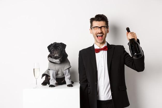 애완 동물, 겨울 방학 및 새해 개념. 크리스마스 파티 애완동물을 축하하는 행복한 남자, 의상을 입은 귀여운 강아지와 함께 서서 샴페인을 마시고 기뻐하며 흰색 배경