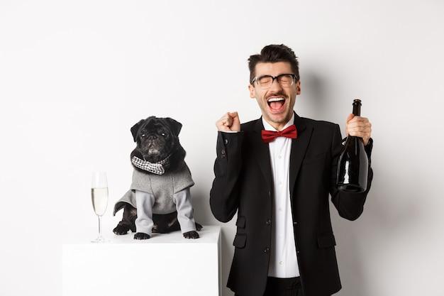ペット、冬休み、年末年始のコンセプト。パーティーの衣装を着て、ボトルのシャンパン、白い背景を保持しているかわいい黒犬とクリスマスを祝う幸せな若い男。
