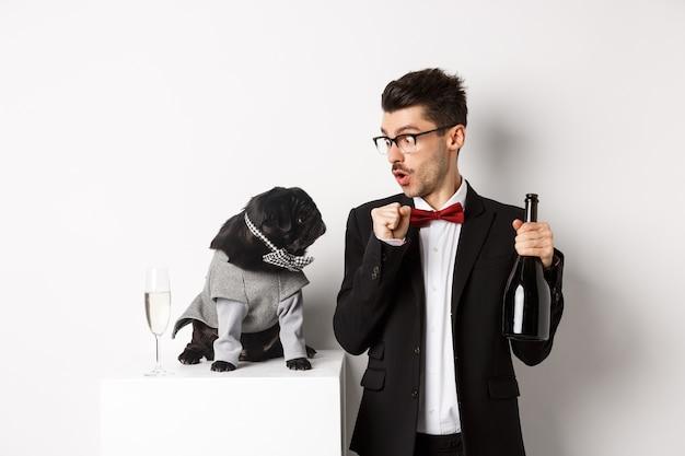 Animali domestici, vacanze invernali e concetto di capodanno. felice giovane che celebra il natale con un simpatico cane nero che indossa un costume da festa, cucciolo che guarda il proprietario, sfondo bianco.