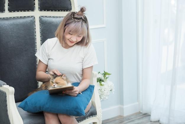 Счастливая молодая азиатская женщина с таблеткой в ее руках и petting котенком сидя на софе