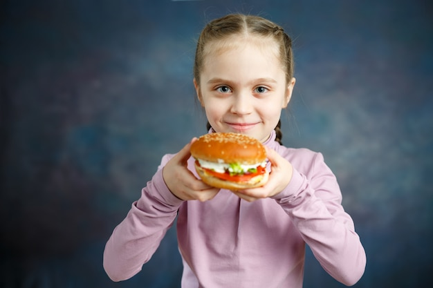 Petty little girl eating burger, following fastfood - image