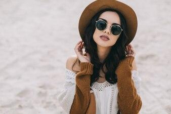 Petty woman sitting on sand