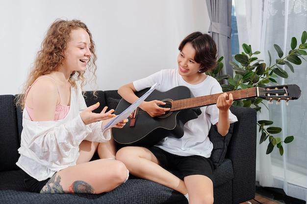 그녀의 여자 친구가 기타를 연주 할 때 노래를 부르는 사소한 젊은 웃는 곱슬 여자