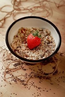 Оловянная тарелка с овсом и клубникой на дереве