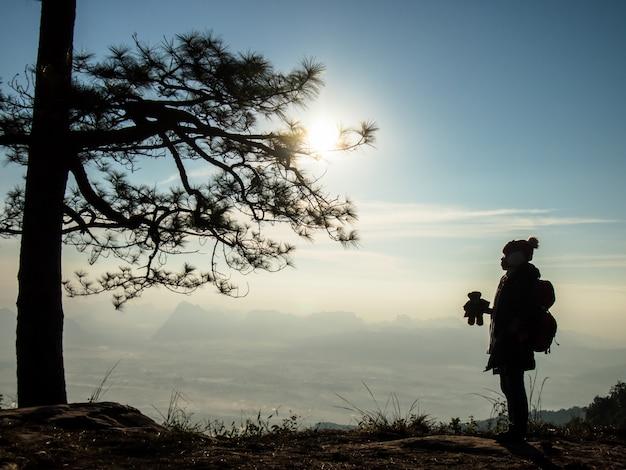 テディー・ベアを保持している観光客は、タイのルーイのプクラドゥエン国立公園のpha nok aenで冬の日の出を見る