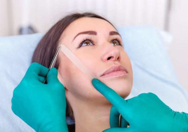 医者は女性の顔、整形手術前のまぶた、眼pha形成をチェックします。
