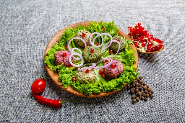 Закуска пхали в виде разноцветных шариков на основе овощей: шпината, цветной капусты и свеклы. блюдо похоже на паштет с соусом из чеснока, зелени, грецких орехов и хмеля-сунели. на сером холсте