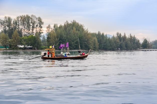 パンガー/タイ-2015年12月23日。タブラム川、タイムアン。タイの漁師は日の出の早朝に釣りに行きます。ジャングルを背景に川沿いに漁船があります。