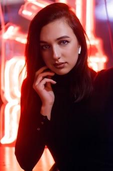 Phantom blue 2020 trend.портрет девушки на фоне неоновой вывески витрины. стиль ретроволны с неоновым и розовым огнями.