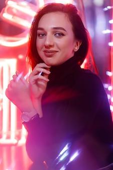 ファントムブルー2020トレンド。ショーウィンドウのネオンサインを背景にした女の子のポートレート。ネオンとピンクのライトを備えたレトロウェーブスタイル。