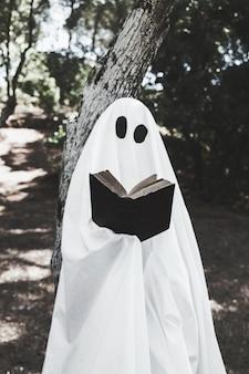Призрак, опираясь на дерево и книгу для чтения