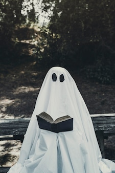 Phantom sitting on bench and reading book