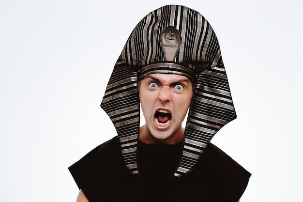 Faraone in antico costume egiziano che si scatena urlando arrabbiato e frustrato in piedi sul muro bianco