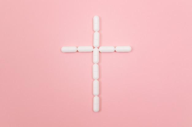 製薬会社は白い錠剤から作られた墓の十字架を傷つけます