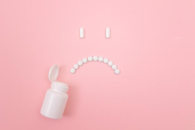 Pharma harm sad smiley face made from white pills