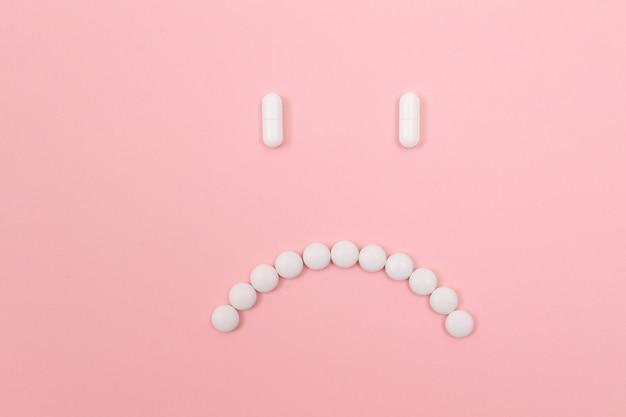 製薬会社は白い錠剤から作られた悲しいスマイリーフェイスを傷つけます