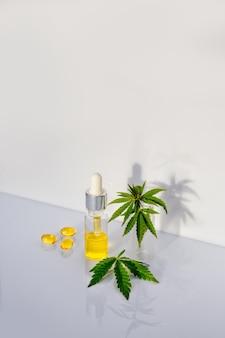 製薬cbdオイルと大麻葉と白い実験室のテーブルの上のカプセル。医療用マリファナと代替医療の概念