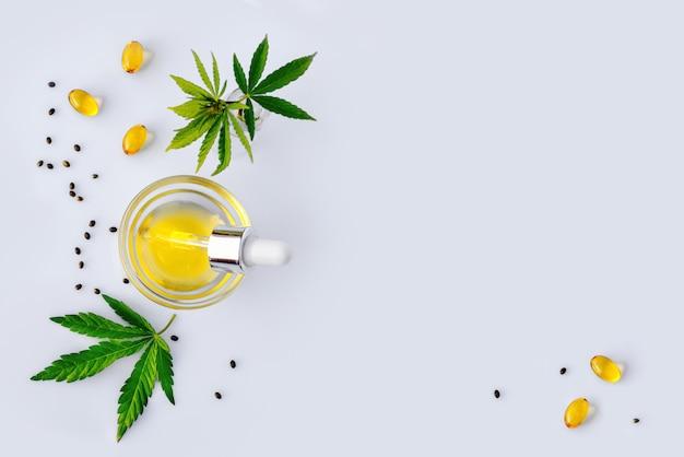 Фармацевтическое масло и капсулы cbd на белом лабораторном столе с листьями каннабиса. концепция медицинской марихуаны и альтернативной медицины