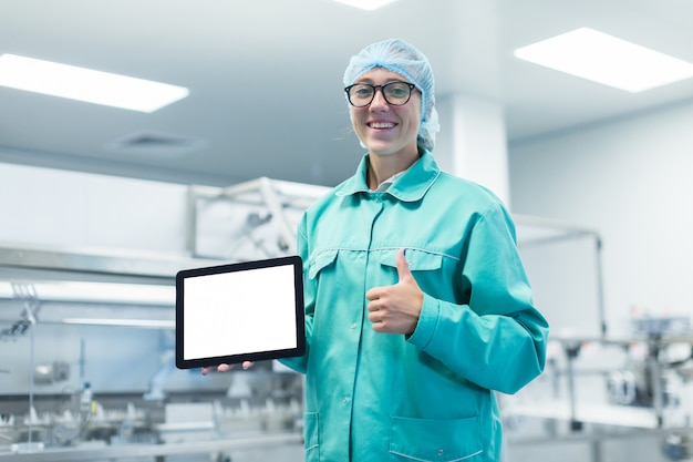Pharmaceutical factory worker with a tablet in his hands shows equipment