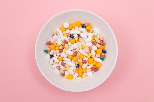 製薬業界と医薬品は白い皿に丸薬を着色しました