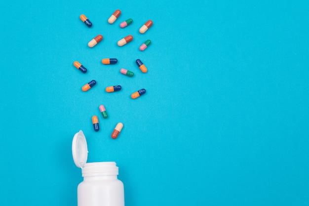 製薬業界と医薬品は青いテーブルの上の丸薬を着色しました