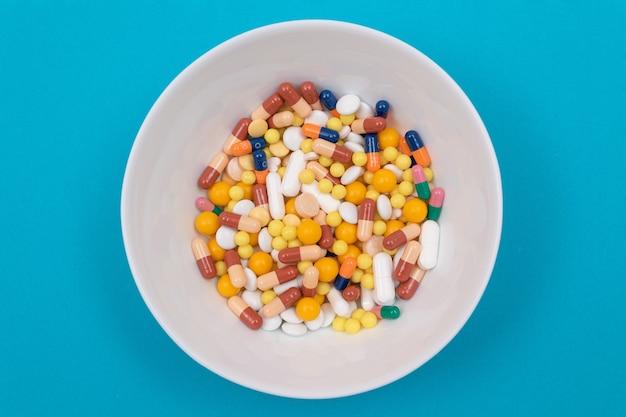 製薬業界と医薬品-プレート上のさまざまな色の錠剤