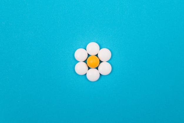 青いテーブルに製薬業界と医薬品の白い錠剤